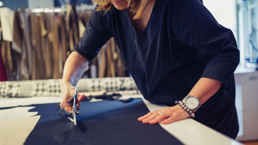 Mature female designer is working in her workshop, cutting material with scissors