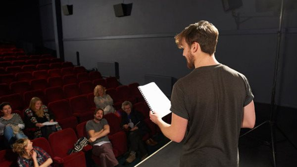 An actor rehearses on stage with his community theatre group as a small audience.