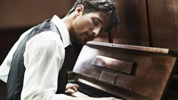 Attractive young pianist playing the piano with passion