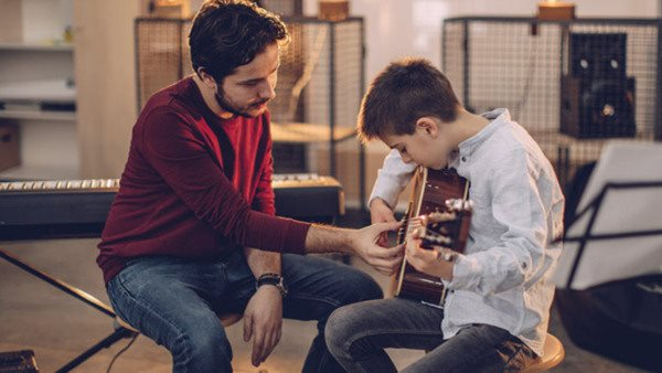 Boy teaching to play guitar in music school