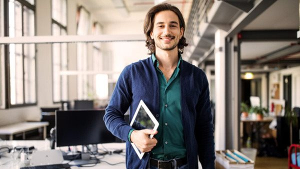 Portrait of smiling young handsome businessman standing with digital tablet at creative office