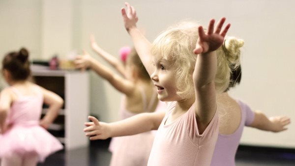 A toddler ballerina, happily focusing on her craft.